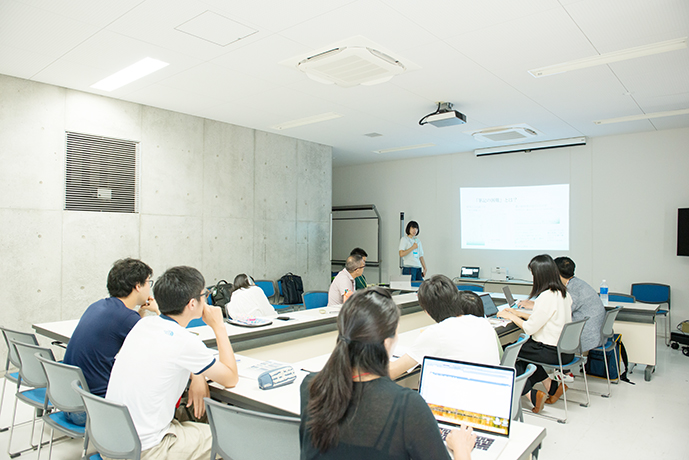 大学のゼミ形式で、スライドを提示し、意見を発表するスカラーたちの様子
