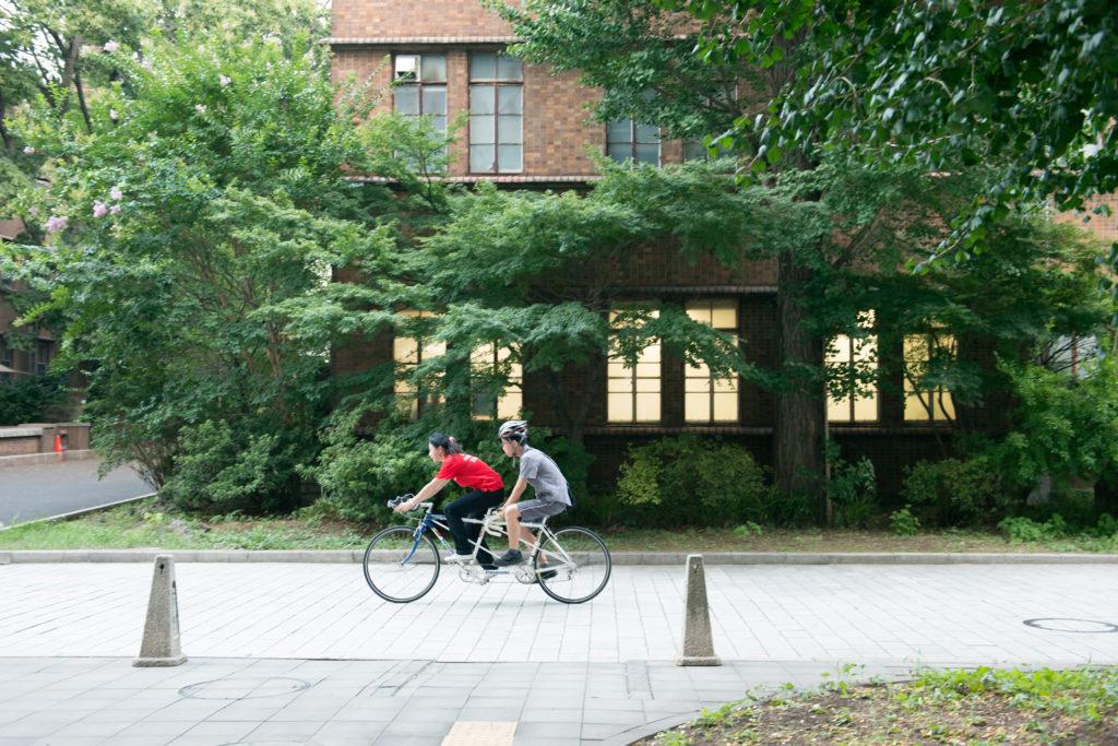 スタッフさんの運転するタンデム自転車の後ろに乗るスカラー。